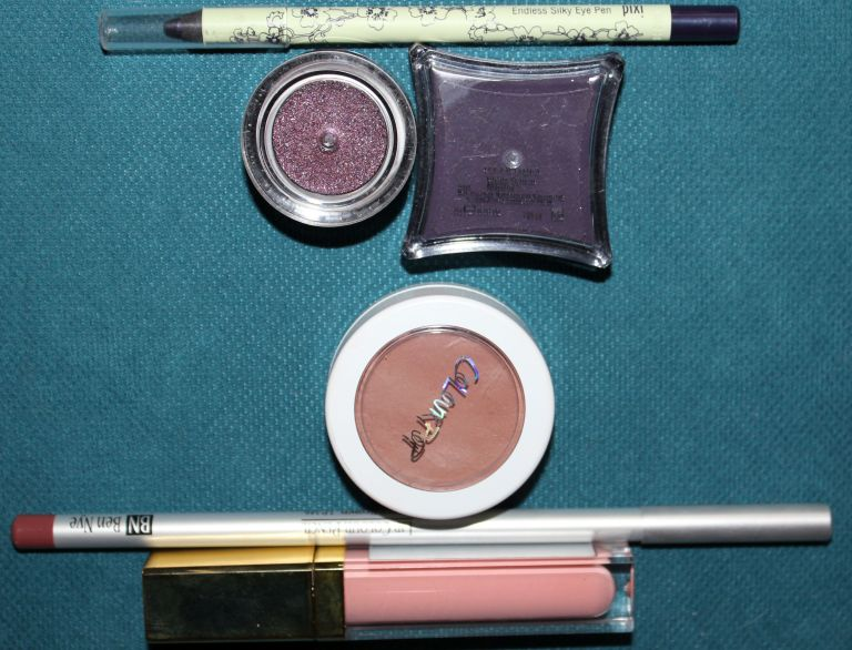 Top to Bottom: Pixi Endless Silky Eye Pen in Black Tulip, ELF Studio Long-Lasting Lustrous Eye Shadow in Festivity, Illamasqua  Cream Pigment in Mould, Colour Pop Super Shock Cheek in Aphrodisiac, Ben Nye Lip Colour Pencil in Berry Brown, Gerard Color Your Smile Lighted Lip Gloss in Spring Fling